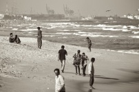 Local people and a beggar on Marina Beach, Chennai, India