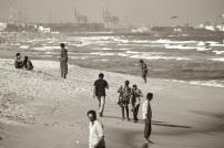 Local people and a beggar on Marina Beach, Chennai, India