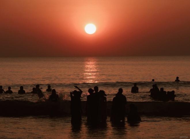 People swimming during sunset in Gokarn Beach
