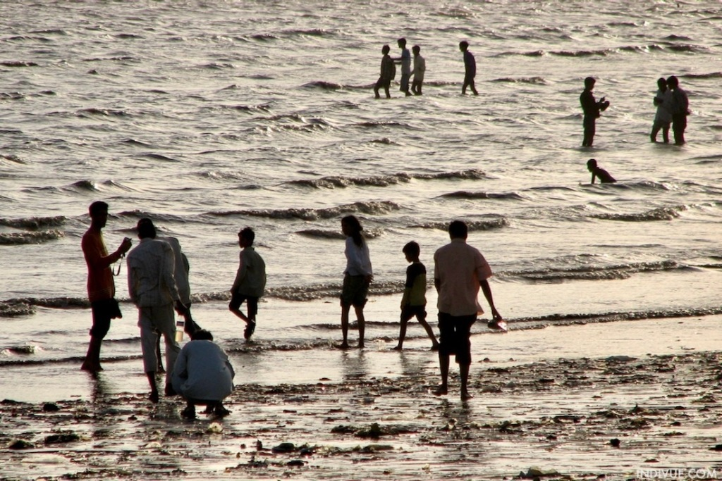 People wade in the water on the beach of Mumbai